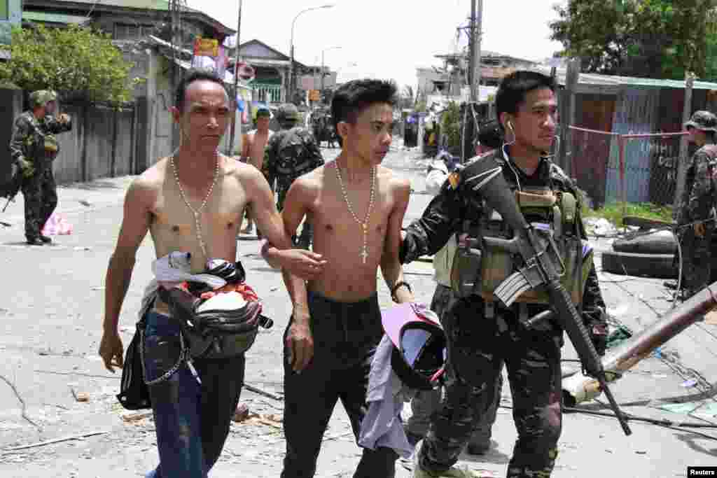 Government soldiers escort residents who were taken hostage and used as human shields by Muslim rebels of Moro National Liberation Front in Zamboanga city, Philippines, Sept. 17, 2013.