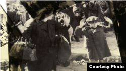 "Nazi photo of Jewish boy surrendering as Nazi troops force Jews out of the Warsaw ghetto in April 1943, displayed at Yad Vashem's ""Flashes of Memory"" exhibition in Jerusalem, January 24, 2018."