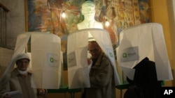 Граждане Грузии покидают избирательные кабинки, проголосовав на президентских выборах. Тбилиси. 27 октября 2013 г.
