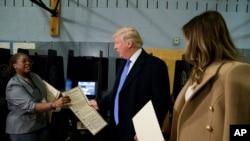 川普夫妇把自己的选票交给选举工作者(2016年11月8日)