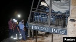 Firefighters, police officers and court experts examine the scene where a balcony of the Barracuda restaurant collapsed onto the Piccolo Padre pizzeria beneath it in St Julian's, outside Valletta, Malta, May 16, 2016.
