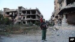 Un combattant tenant le drapeau libyen devant des bâtiments endommagés à Benghazi, en Libye, le 23 février 2016.