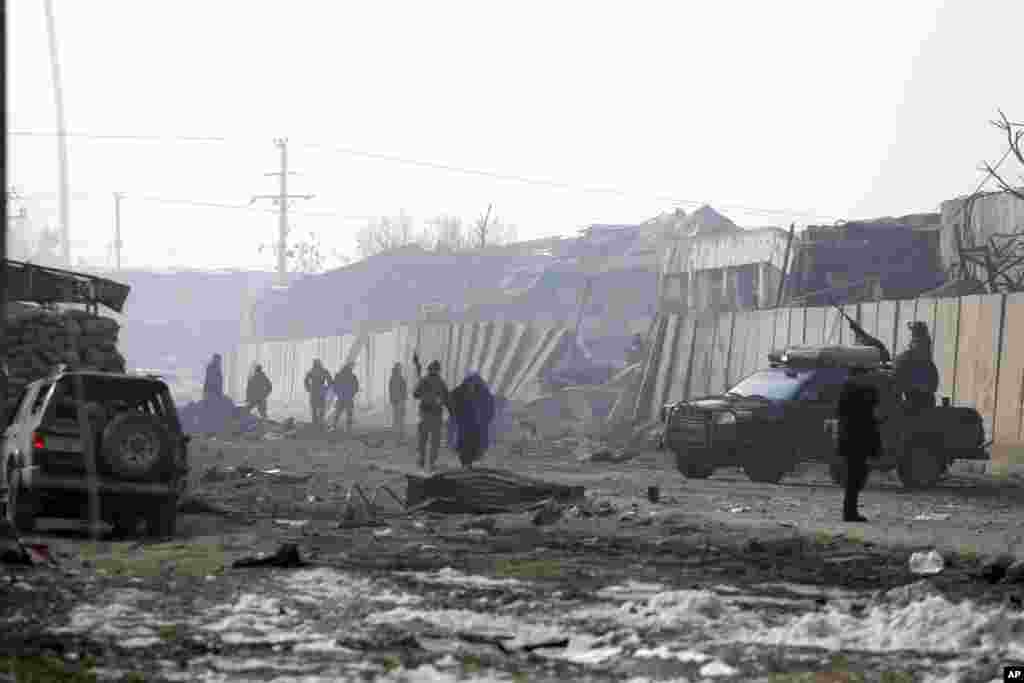 Afghan security forces gather the next day at the site of an attack in Kabul. A Taliban suicide bomber detonated an explosive-laden vehicle in the capital on January 14, 2019, say officials.