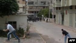 Các thanh niên Syria ném đá vào cảnh sát chống bạo loạn