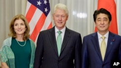 From left, U.S. Ambassador to Japan Caroline Kennedy, and former U.S. President Bill Clinton, center, pose with Japanese Prime Minister Shinzo Abe prior to a dinner held by Abe at the latter's official residence in Tokyo, Japan, March 17, 2015.
