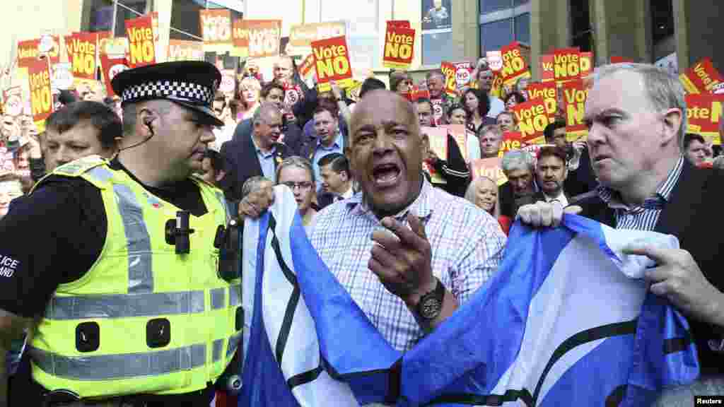 "Supporters of the ""Yes"" campaign in Glasgow, Scotland, encounter a police officer as they try to disrupt a ""No"" campaign rally where the leader of the Labour party, Ed Milibrand, was to make a speech."