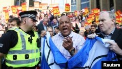 "Supporters of the ""Yes"" campaign are confronted by a police officer as they try to disrupt a ""No"" campaign rally. The leader of the Labour party Ed Miliband was to address in Glasgow, Scotland on Sept. 11, 2014"
