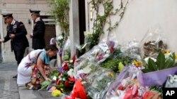 Una mujer coloca flores frente a la estación de Carabineros en la que revistaba Mario Cerciello Rega, Roma, sábado 27 de julio de 2019. Dos estadounidenses de 19 años fueron arrestados como presuntos autores de la muerte a puñaladas de Cerciello Rega.