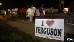 """Sebuh tanda berbunyi """"Saya Cinta Ferguson"""" sementara pada latar belakang tampak para pengunjuk rasa berjalan di kota Ferguson (21/8/2014)."""