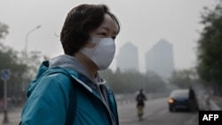 A woman wears a protective mask to fight bad air pollution in Beijing on October 22, 2018. (Photo by Nicolas ASFOURI / AFP)
