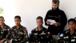 9일 시리아 다라 주에서 한 남성이 네 명의 피랍된 필리핀 병사들을 앞에 두고 성명을 읽다