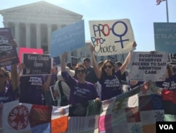Pro-choice demonstrators wave signs and make their voices heard after the Supreme Court upheld abortion rights in a 5-3 decision, in front of the Supreme Court building in Washington, June 27, 2016. (J. Oni / VOA News)