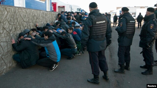 Russian police detain migrant workers during a raid at a vegetable warehouse complex in the Biryulyovo district of Moscow, Oct. 14, 2013.