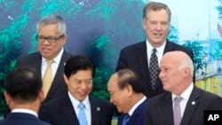 Thủ tướng Việt Nam Nguyễn Xuân Phúc (giữa phải) bắt tay Bộ trưởng Thương Mại Trung Quốc Chung Sơn (giữa trái). Đại diện Thương mại Mỹ Robert Lighthizer đứng ở trên bên phải.