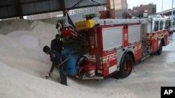Petugas pemadam kebakaran di New York mengisi garam ke dalam wadah di truk mereka yang akan digunakan untuk mencairkan es (8/2). (AP/Mary Altaffer)