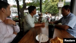 Men drink coffee and have breakfast at a coffee store in Phnom Penh, Cambodia July 19, 2018. (REUTERS/Samrang Pring)