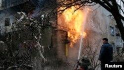 Seorang petugas pemadam kebakaran tengah berupaya memadamkan api di rumah penduduk di wilayah Donetsk, Ukraina Timur (9/2).