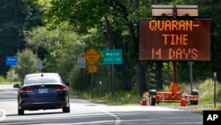 In this Wednesday, June 10, 2020, photo, a sign in Gilead, Maine, near the border with New Hampshire, warns visitors entering Maine that they are required to quarantine for 14 days. Residents of New Hampshire and Vermont are exempt. (AP Photo/Robert F. Bu