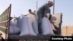 FILE - Sacks of processed corn are loaded on trucks outside Raqqa, Syria, Oct. 23, 2016. (Credit: Dawa al-Haq)