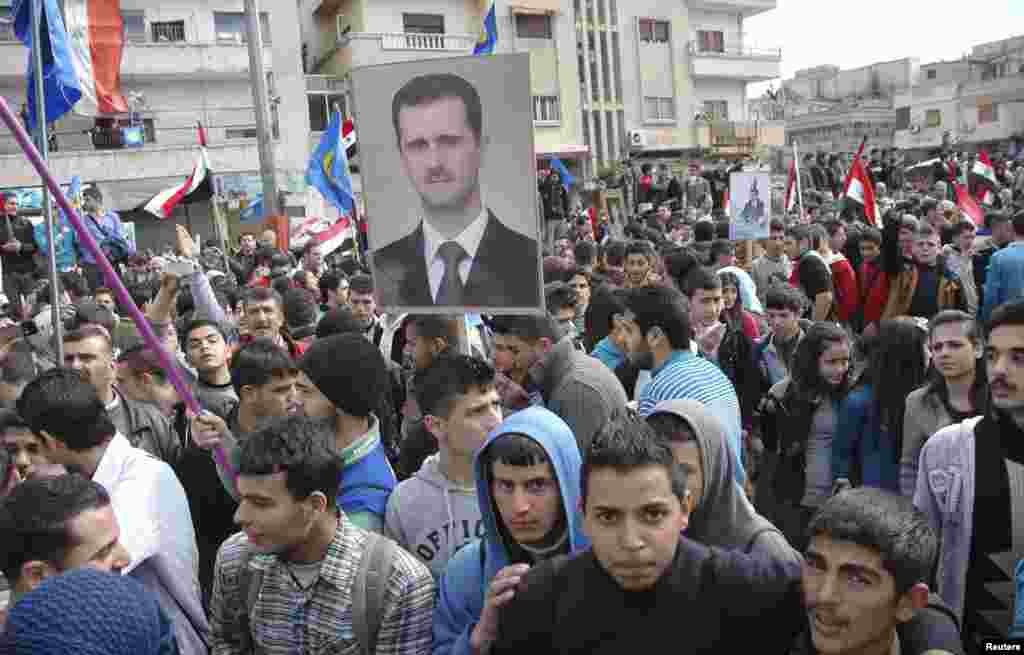Supporters of Syrian President Bashar al-Assad rally in Homs, Feb. 11, 2014, in this handout photograph released by SANA.