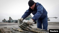 A serviceman checks ammunition next to Sukhoi Su-25 jet fighters during a drill at the Russian southern Stavropol region.