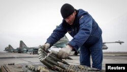 FILE - A serviceman checks ammunition next to Sukhoi Su-25 jet fighters during a drill at the Russian southern Stavropol region, just north of Abkhazia.