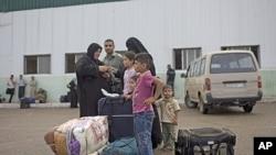 一个巴勒斯坦家庭周六等待跨过拉法边境站,进入埃及