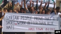 Syrians flashing the victory sign during an anti-regime demonstration in Hass in the restive northern province of Idlib on June 8, 2012.