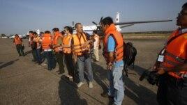 Nhân viên cứu hộ và các nhà báo tập trung trước máy bay An-26 chuẩn bị công tác tìm kiếm chiếc máy bay Malaysia bị mất tích tại sân bay quân sự của Việt Nam ở TPHCM, ngày 10/3/2014.