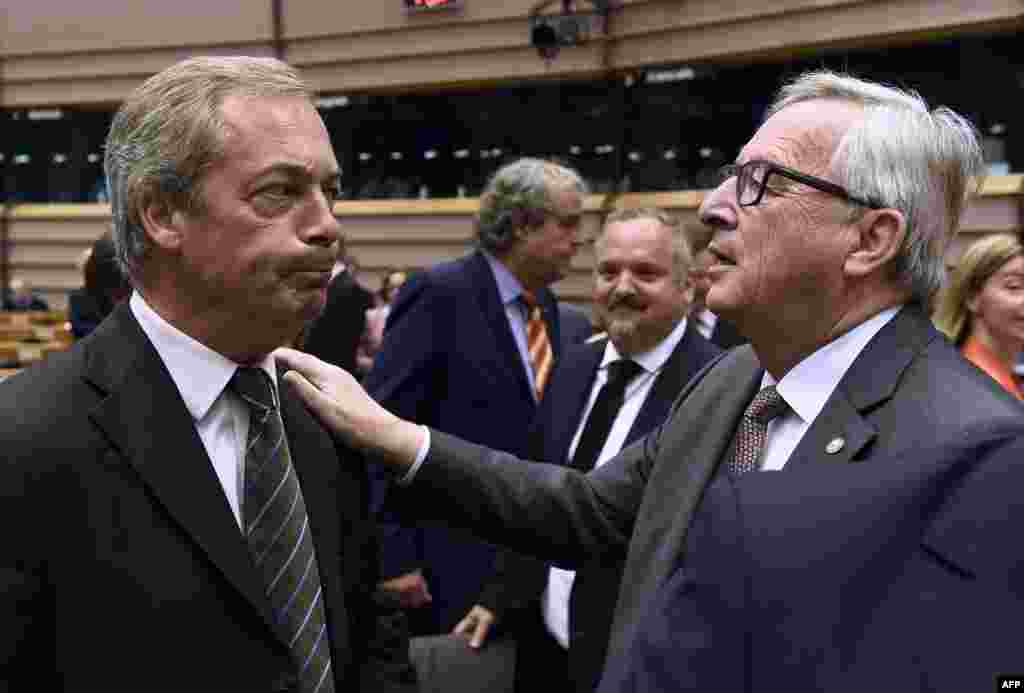 UK Independence Party (UKIP) leader Nigel Farage (L) talks with EU Commission President Jean-Claude Juncker before a plenary session at the EU headquarters in Brussels, Belgium. Juncker called on Prime Minister David Cameron to clarify quickly when Britain intends to leave the EU, saying there can be no negotiation on future ties before London formally applies to exit.
