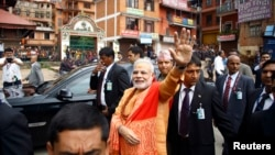 India's Prime Minister Narendra Modi waves at supporters waiting to greet him at the premises of Pashupatinath Temple in Kathmandu, Aug. 4, 2014.