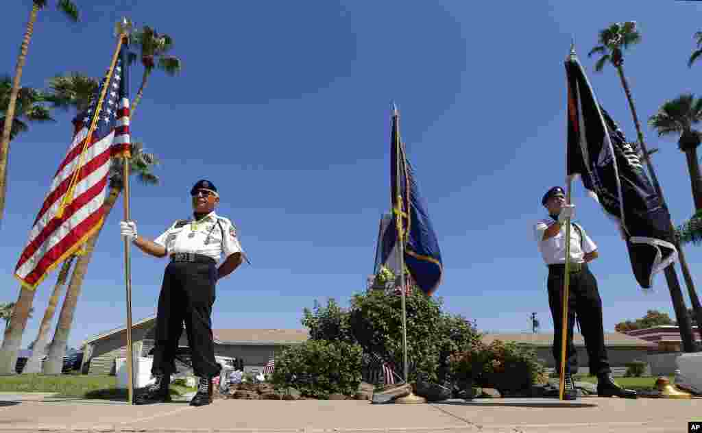 Members of the POW-MIA-KIA Honor Guard organization stand in front of a local mortuary keeping the late Arizona Sen. John McCain, Aug. 26, 2018, in Phoenix.
