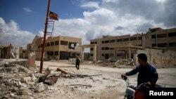 一名骑摩托车的人和一名男子在叙利亚东古塔被反政府组织控制的一个城区的街道上。(2016年4月13日)