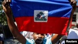 Yon manifestan lanse slogan pandan lap pote drapo ayisyen an pandan yon manifestasyon kont Prezidan Ayiti a