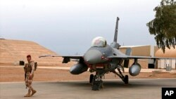 Seorang tentara irak berjaga dekat sebuah pesawat jet tempur F-16 di Pangkalan Udara Balad, Irak, 13 Februari 2018. Pada Minggu, 18 April 2021, lima roket menghantam pangkalan itu. (Foto: AP/arsip)