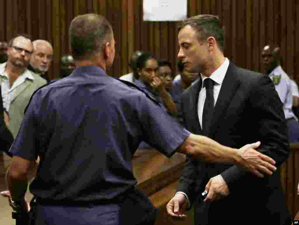 Oscar Pistorius, right, is led out of court in Pretoria, South Africa, Tuesday, Oct. 21, 2014.