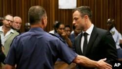 Atlet Afrika Selatan Oscar Pistorius (kanan) dibawa keluar ruang sidang di Pretoria (21/10). (AP/Themba Hadebe)