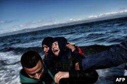 ຊາຍຄົນນຶ່ງກຳລັງປອບໃຈ ຍິງສາວຄົນນຶ່ງ ພ້ອມດ້ວຍຊາວອົບພະຍົບ ຈຳນວນນຶ່ງ ທີ່ຫາກໍເດີນທາງໄປຮອດ ເກາະ Lesbos ຂອງກຣິສ ເມື່ອວັນທີ 25 ຕຸລາ 2015 ຫຼັງຈາກທີ່ພວກເຂົາເຈົ້າ ໄດ້ຂ້າມທະເລ Angean ຈາກເທີກີ.