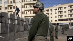 Egyptian army soldiers stand guard in front of the presidential palace, in Cairo, December 9, 2012.