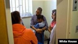 El presidente Obama conforta a su hija menor Sasha, durante la visita a la celda de Mandela en la Isla Robben, junto a su hija Malia y la primera dama Michelle Obama.