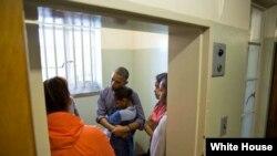 Photo d'archives : Le président Barack Obama et la Première Dame Michelle, avec leurs filles Sasha et Malia, dans la cellule de l'ancien président sud-africain Nelson Mandela, écoutant l'ancien prisonnier Ahmed Kathrada, lors d'une visite à la prison de Robben Island au Cap, en Afrique du Sud, 30 juin 2013.