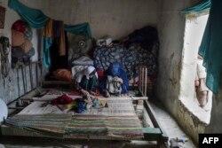 Perempuan pengungsi Afghanistan membuat karpet di rumah mereka di sebuah kamp pengungsi di Peshawar. (Foto: AFP)