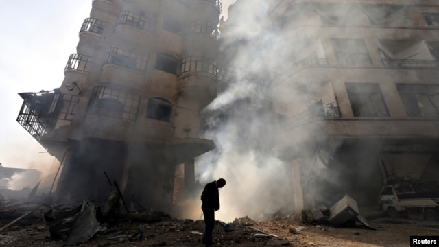 A man walks in front of a burning building after a Syrian Air force air strike in the Ain Tarma neighborhood of Damascus January 27, 2013.