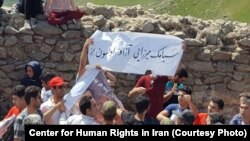 In this undated photo published by the U.S.-based Center for Human Rights in Iran, Iranian Azerbaijanis stage an annual July protest against discrimination targeting their community at Babak Fort in East Azerbaijan province. The slogan on the white banner calls for the release of a detained Azeri rights activist, Siamak Mirzaei.