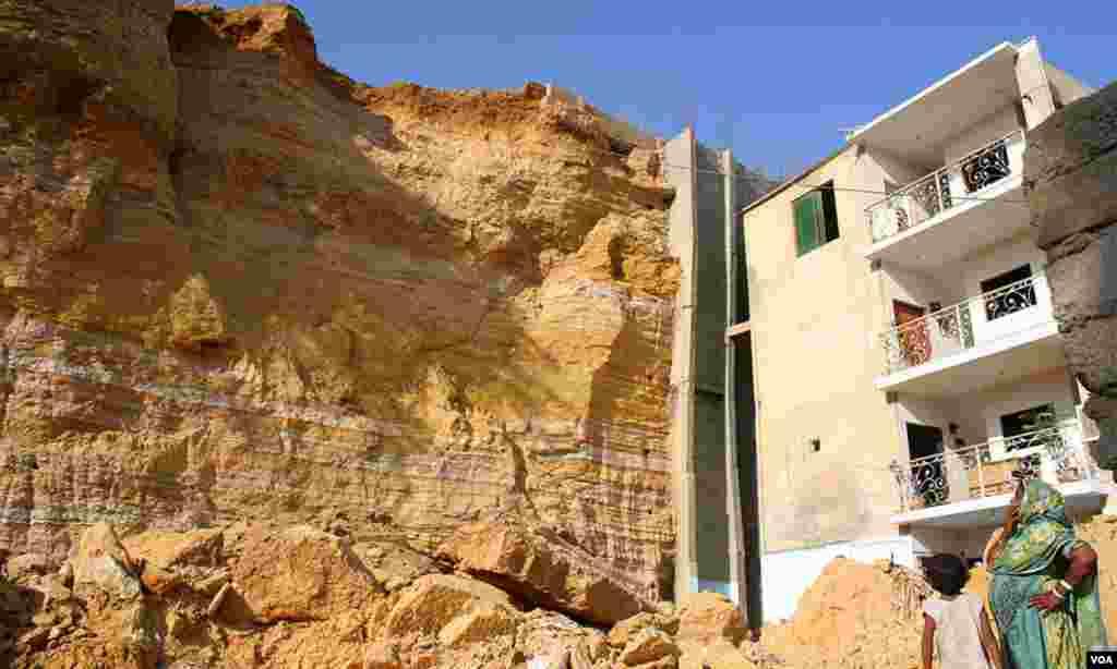 متاثرہ پلاٹ کے کونے پر بنا ہوا ایک اور مکان جس کے عقب میں کنکریٹ کی دیوار بھی دیکھی جا سکتی ہے۔