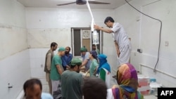 In this photograph released by Medecins Sans Frontieres (MSF) on October 3, 2015, Afghan MSF surgeons work in an undamaged part of the MSF hospital in Kunduz after the operating theaters were destroyed in an airstrike.