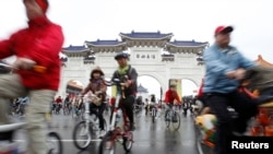 People cycle their bicycles at the Chiang Kai-shek Memorial Hall in Taipei December 31, 2011.