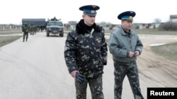 Ukrainian officers return after negotiations with Russian troops (L) at the Belbek airport in the Crimea region, March 4, 2014.