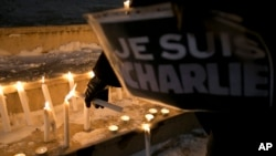 "A woman holding a sign that read in French ""I am Charlie"" lights a candle during a demonstration in solidarity with those killed in an attack at the Paris offices of the weekly newspaper Charlie Hebdo in Kosovo capital Pristina, Wednesday, Jan. 7, 2015."