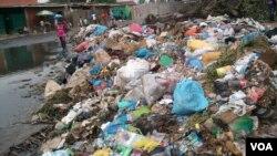 Angola, Luanda. Uma mulher atravessa o amontoado de lixo de galochas calçadas. 25 de Abril de 2014 (imagem de arquivo)